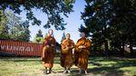 From left, Tan Sampanno, Ajahn Kassapo and Ajahn Sudanto make their morning alms round throughWhiteSalmon.